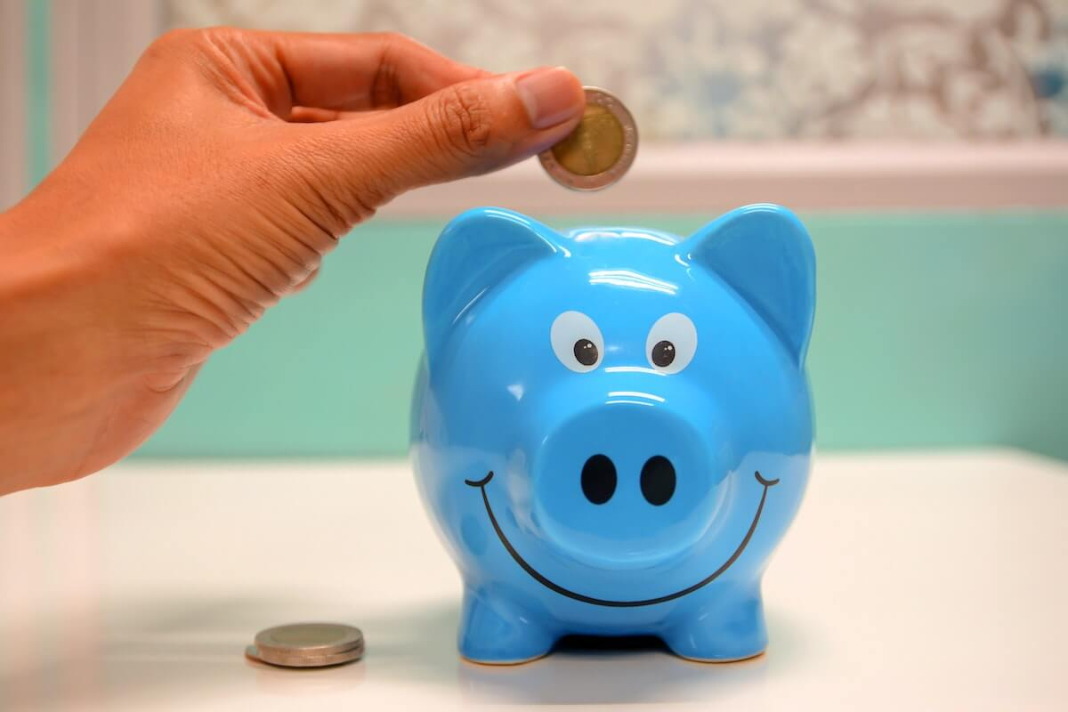 someone dropping a coin into a blue piggy bank