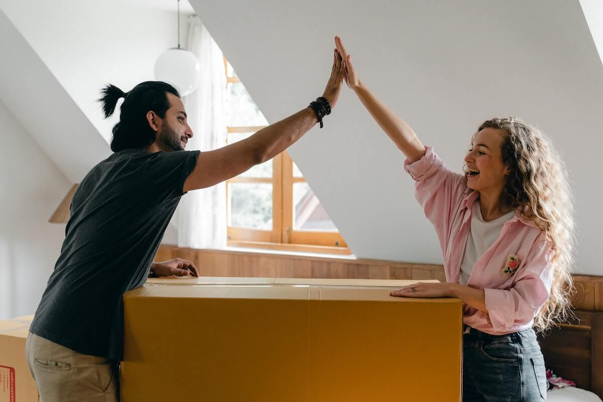 male and female high five over moving box